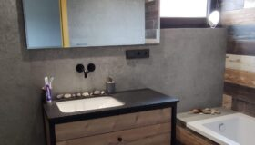 Szafka łazienkowa na stalowej ramie z drewnianymi bokami.